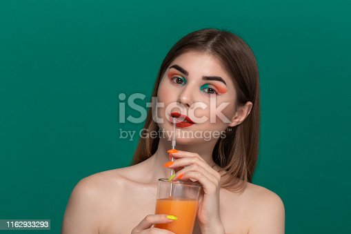 istock Closeup portrait of beautiful young woman with bright color make-up drinking orange juice 1162933293