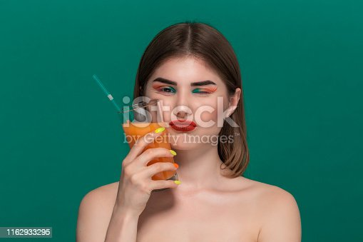 istock Closeup portrait of beautiful young woman with bright color make-up holding orange juice near the face 1162933295