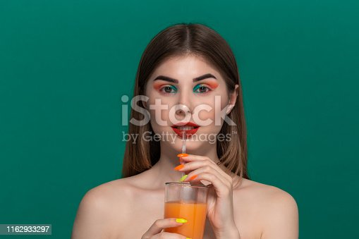 istock Closeup portrait of beautiful young woman with bright color make-up drinking orange juice 1162933297