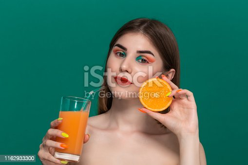 istock Closeup portrait of beautiful young woman with bright color make-up with orange juice holding half of an orange near the face. 1162933300