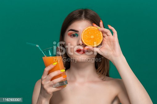 istock Closeup portrait of beautiful young woman with bright color make-up drinking orange juice 1162933301