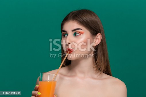istock Closeup portrait of beautiful young woman with bright color make-up drinking orange juice 1162933303