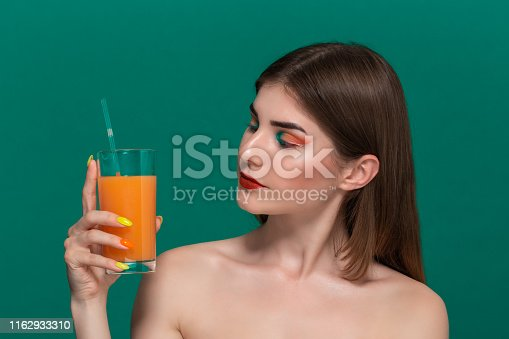 istock Closeup portrait of beautiful young woman with bright color make-up holding orange juice near the face 1162933310