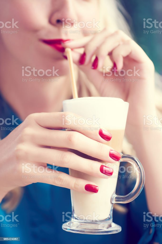 Closeup portrait of blonde woman in the blue dress sitting at the cafe and drinking milk cocktail. Beauty portrait royalty-free stock photo