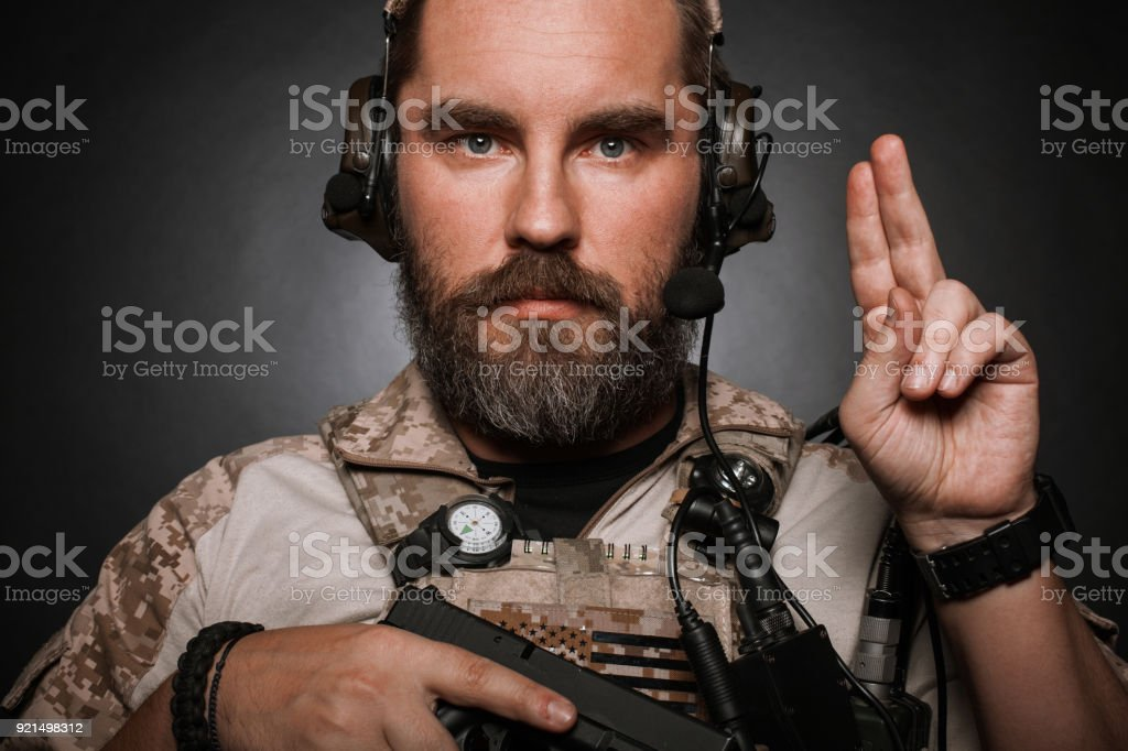 Close-up portrait of brutal bearded man in military desert uniform and body armor who holds his gun on black background. Studio photography of a player in airsoft stock photo