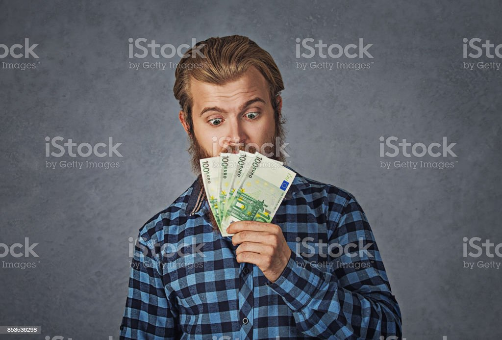 Closeup portrait of business man executive, CEO, boss, corporate employee holding euro banknotes tightly, isolated on grey background. Negative human emotion facial expression stock photo