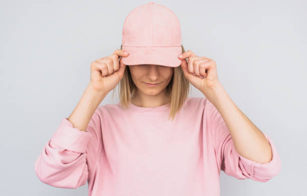 Closeup portrait of Caucasian blonde young female wearing pink sweater and cover her eyes with pink cap, protect from the sun rays, isolated on white studio background. Positive people emotion concept Closeup portrait of Caucasian blonde young female wearing pink sweater and cover her eyes with pink cap, protect from the sun rays, isolated on white studio background. Positive people emotion concept baseball cap stock pictures, royalty-free photos & images