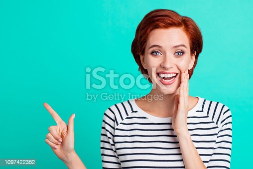Close-up portrait of charming attractive cheerful positive red-haired lady in striped pullover pointing aside up copy space rumour isolated over bright vivid shine green turquoise background