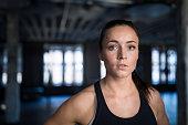 Close-up portrait of confident athlete in gym.