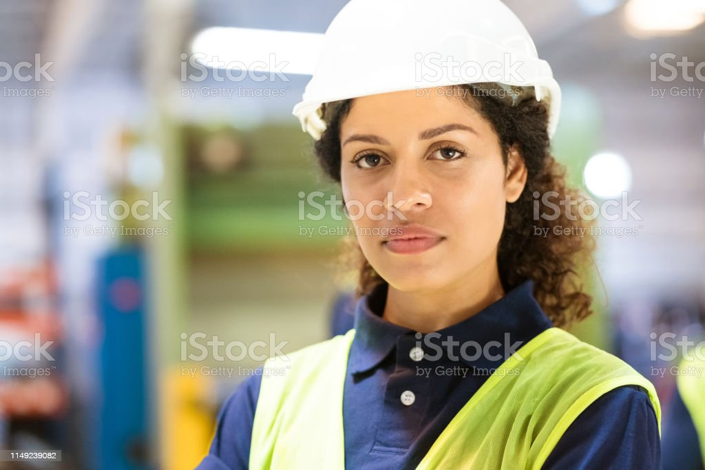Close-up portrait of confident female worker Portrait of confident worker wearing hardhat. Close-up of female standing in factory. She is in reflective clothing. 30-34 Years Stock Photo