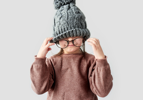istock Closeup portrait of cute funny little girl playing in the winter warm hat, wearing sweater with round stylish spectacles on a white studio background. 1089381856