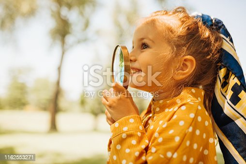 istock Closeup portrait of cute happy little girl playing and exploring with magnifying glass the nature outdoor. Curious child looking through magnifier on a sunny day in park. Childhood 1162553271