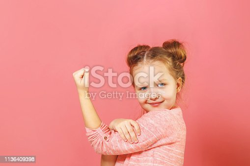 Closeup portrait of cute kid with hair buns over pink background. Child hand on biceps show how girl power