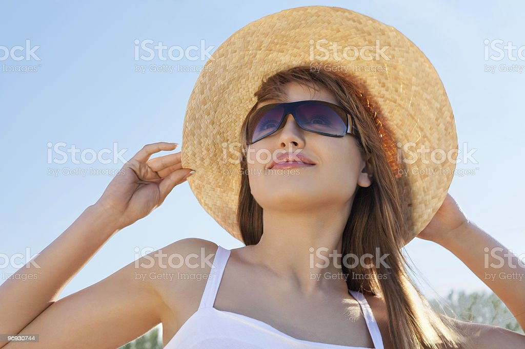 Closeup portrait of cute young woman wearing a straw hat royalty-free stock photo