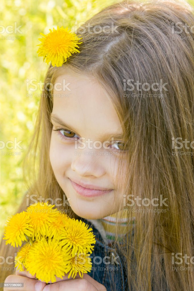 Close-up portrait of eight-year-old girl with dandelions in hands stock photo