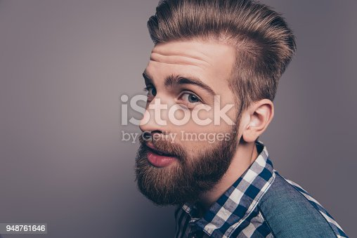 636829368istockphoto Closeup portrait of funny glad hipster bearded man looking at camera, side-view photo 948761646