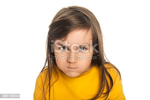 istock Close-up portrait of furious teenage girl looking at camera with serious facial expression against white background 895746534