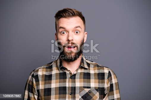 1092211952 istock photo Close-up portrait of handsome attractive bearded young serious brunet men wearing casual shirt, showing shocked facial expression. Isolated over grey background 1059057882