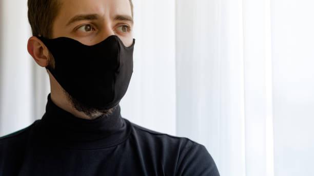 Nahaufnahme Porträt von schönen kaukasischen Mann mit wiederverwendbaren schwarzen Gesichtsmaske. Konzept mit Copyspace in Innenräumen – Foto