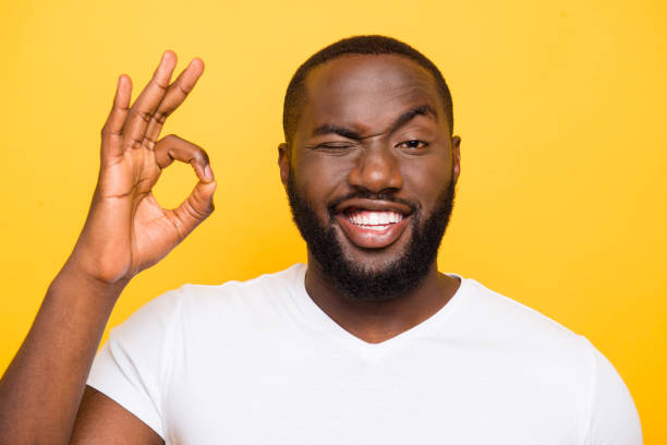 close-up portrait of handsome glad mulatto bearded funky guy showing ok-sign, isolated over bright vivid yellow background - blinking stock pictures, royalty-free photos & images