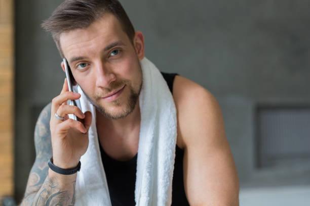 closeup portret van knappe man bel gsm in sportschool - call center stockfoto's en -beelden