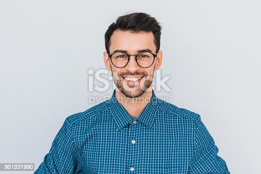 istock Closeup portrait of handsome smart-looking smiling with toothy smile male posing for social advertisement, isolated on white background with copy space for your promotional information or content. 951331990