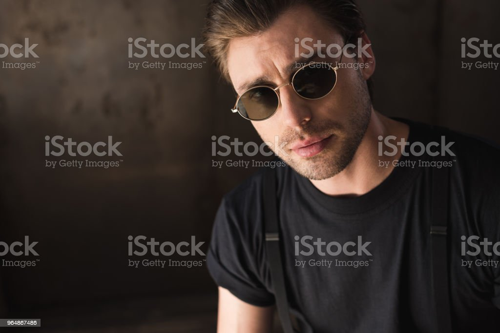 close-up portrait of handsome young man in black t-shirt and sunglasses looking at camera royalty-free stock photo