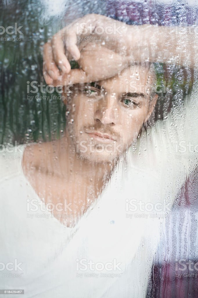 Closeup portrait of handsome young man looking through wet window stock photo