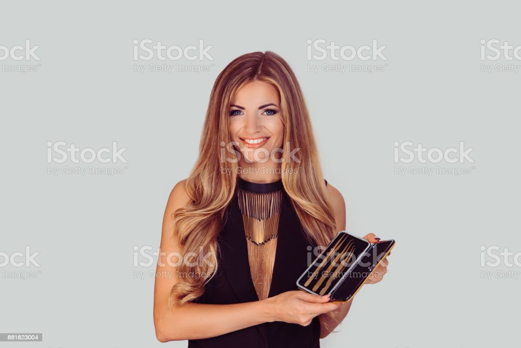 Closeup portrait of happy beautiful girl woman holding tools for eyebrows eyelashes extensions on light grey white background. Positive face expression emotion body language stock photo