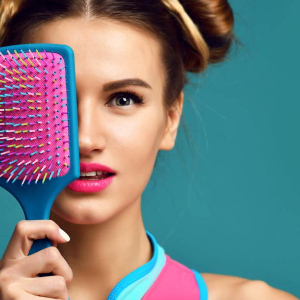 closeup portrait brünette frau glücklich mode schließen augen mit bunten rosa blau gelb große kamm haarbürste - kamm stock-fotos und bilder