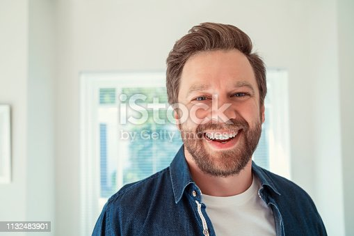 Close-up of joyful mid adult male wearing casuals. Portrait of happy man is having beard. He is in living room.