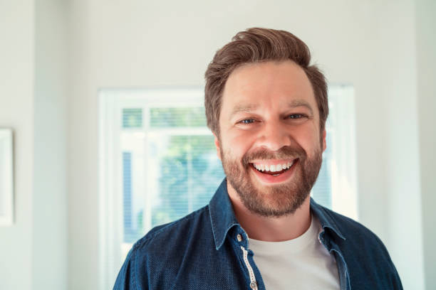 Close-up portrait of happy mid adult man at home stock photo