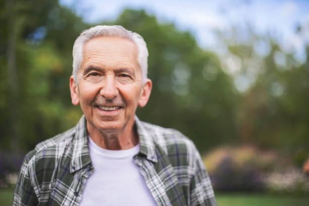 Close-up portrait of happy senior man in back yard stock photo