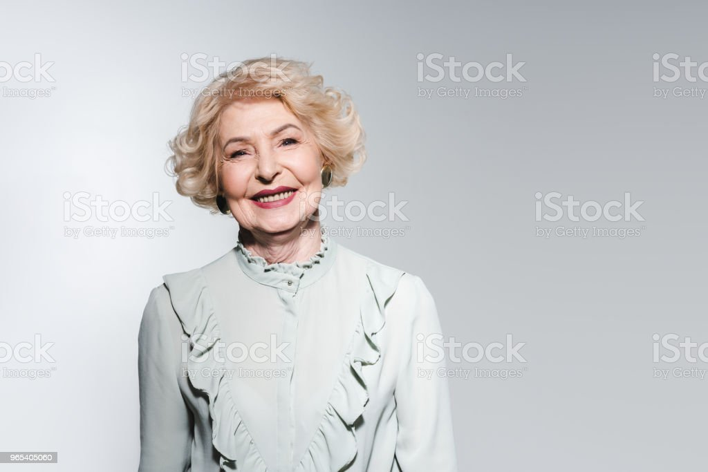 close-up portrait of happy senior woman in stylish shirt isolated on grey zbiór zdjęć royalty-free