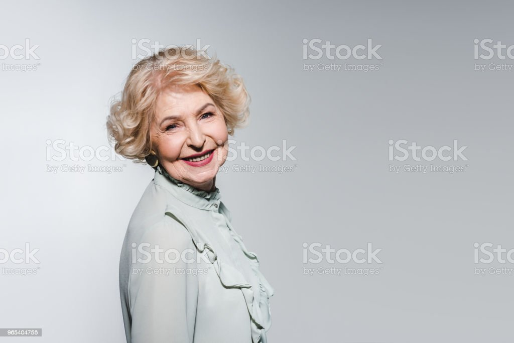 close-up portrait of happy senior woman isolated on grey zbiór zdjęć royalty-free