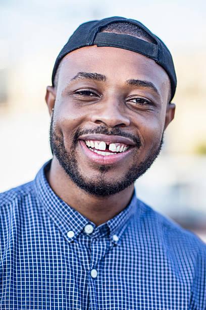 close-up portrait of happy young man outdoors - zahnlücke stock-fotos und bilder