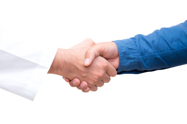 Closeup portrait of healthcare professional doctor shaking hand with patient, isolated on white background. stock photo