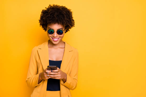 close-up portrait of her she nice attractive lovely focused cheerful cheery addicted wavy-haired girl using cell browsing web 5g app isolated on bright vivid shine vibrant yellow color background - interação com o cliente imagens e fotografias de stock