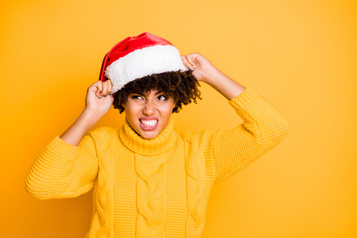 Close-up portrait of her she nice attractive mad angry unsatisfied evil wavy-haired girl putting santa outfit on expressing unpleasant isolated over bright vivid shine vibrant yellow color background