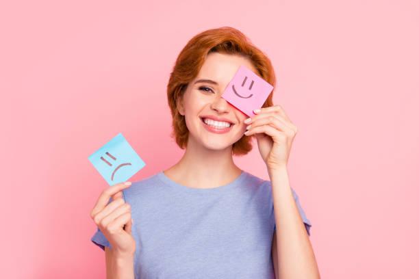 Retrato de cerca de ella agradable Linda encantadora chica alegre atractiva vistiendo camiseta azul casual sosteniendo en las manos dos notas de sorteo positivo buena opción aislada sobre fondo pastel rosa - foto de stock