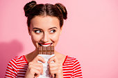 istock Close-up portrait of her she nice cute charming attractive glamorous cheerful sly cunning hungry girl in striped t-shirt biting tasting eating desirable favorite dessert isolated on pink background 1137020395