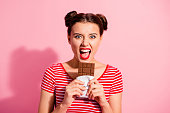 istock Close-up portrait of her she nice cute charming crazy attractive lovely comic childish girl wearing striped t-shirt biting favorite desirable dessert isolated over pink pastel background 1137019768