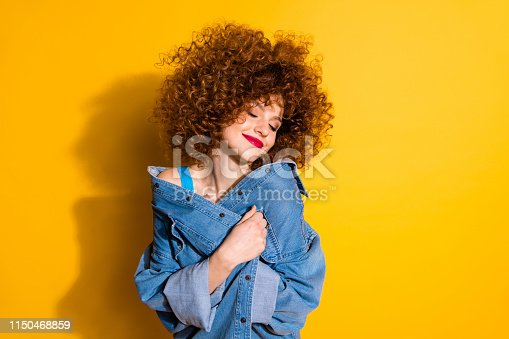 Close-up portrait of her she nice cute lovely charming attractive winsome sweet cheerful wavy-haired girl covering cosy jacket isolated over bright vivid shine yellow background.