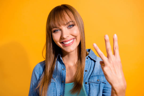 close-up portrait of her she nice cute sweet lovely winsome fascinating attractive cheerful straight-haired lady showing 3 middle fingers isolated over bright vivid shine yellow background - terceira imagens e fotografias de stock