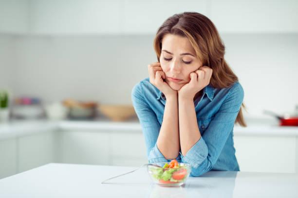 特寫鏡頭的她她可愛可愛的迷人的傷心無聊無聊失望棕色頭髮的女士在淺白色室內風格的廚房裡看著新的綠色排毒維生素沙拉 - 飢餓的 個照片及圖片檔