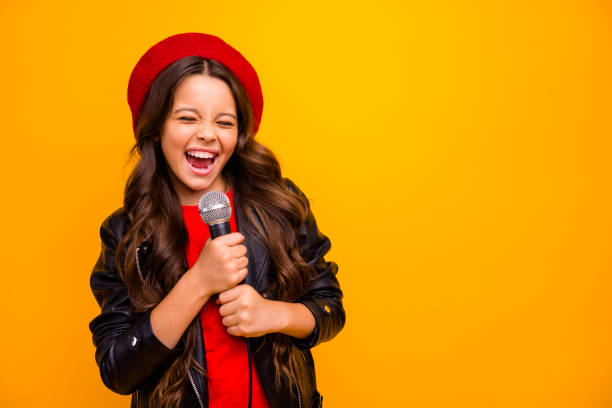 Close-up portrait of her she nice-looking attractive charming trendy fashionable cheerful wavy-haired girl singing karaoke hit isolated over bright vivid shine vibrant yellow color background stock photo