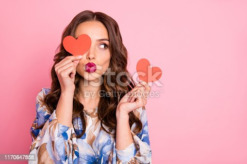 Close-up portrait of her she, nice-looking attractive lovely coquettish cheerful cheery wavy-haired girl holding in hands two small little heart sending you kiss isolated over pink pastel background