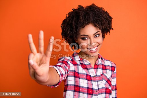 Close-up portrait of her she nice-looking attractive lovely cute cheerful, cheery wavy-haired lady wearing checked shirt giving 3 sign isolated over bright vivid shine orange background