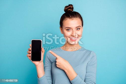 Close-up portrait of her she nice-looking attractive sweet lovely cheerful teenage girl holding in hand new cool buying purchase ad advert isolated over bright vivid shine turquoise background.