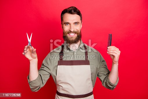 928445950 istock photo Close-up portrait of his he nice attractive cheerful cheery bearded guy salon owner holding in hands instruments choose choice isolated over bright vivid shine red background 1167728268
